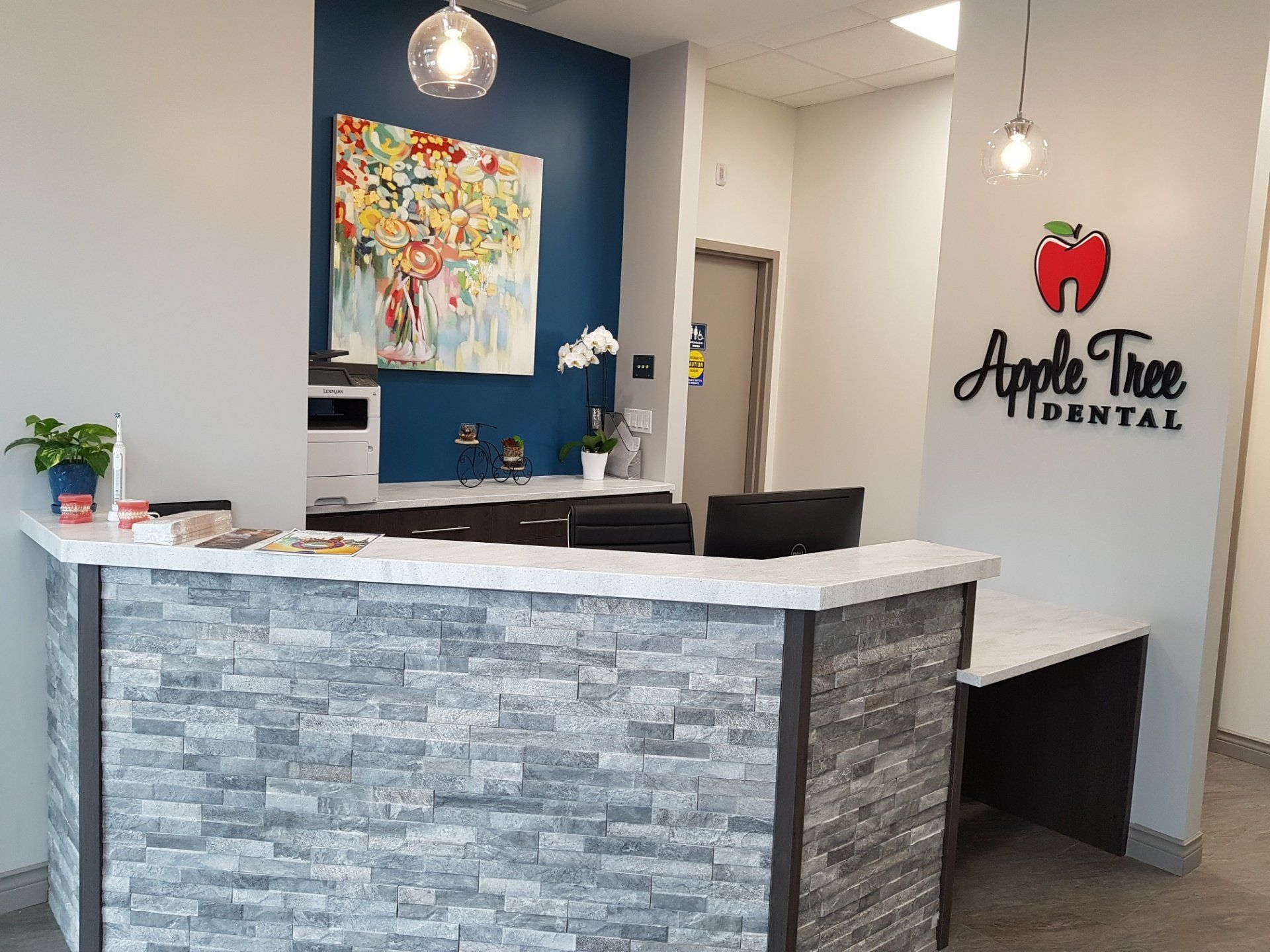Reception area of Apple Tree Dental having wall painting and reception desk along with chairs