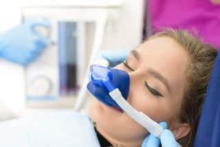 Dentist sedating the female patient