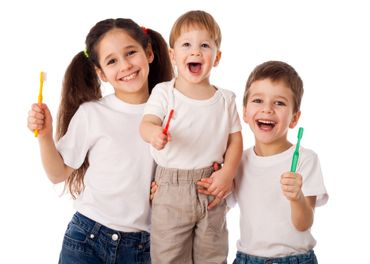 Three happy kids holding toothbrushes