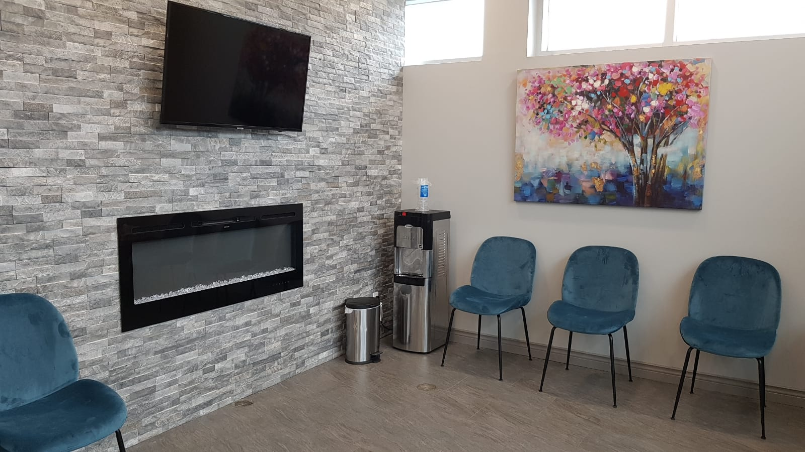 Waiting area with Tv, water dispenser and the chair with painting on the wall