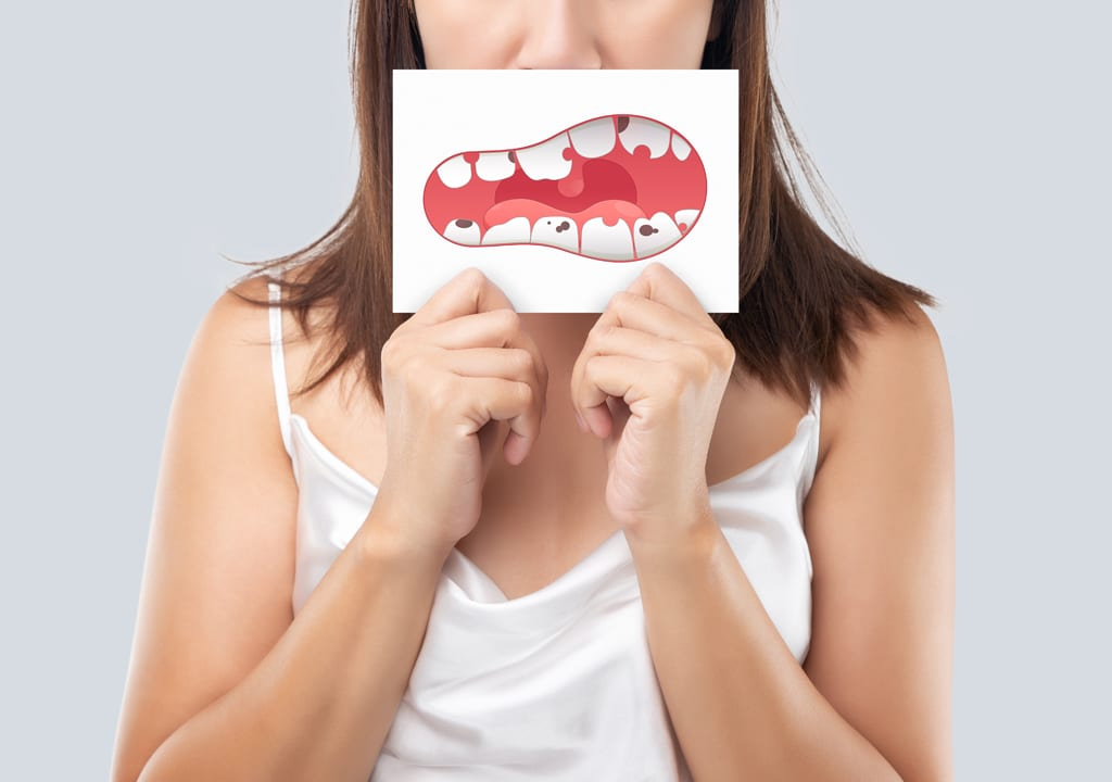 Girl is holding the image of broken teeth